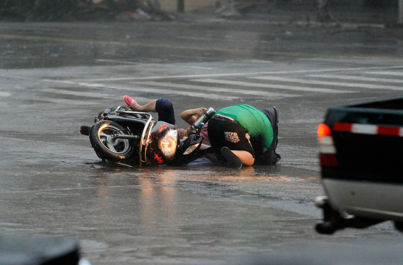 mujer y hombre tirados en la carretera junto a su moto